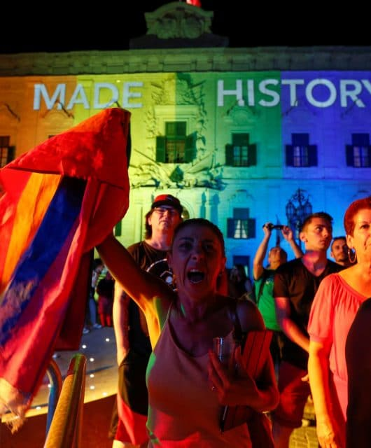 People celebrate in front of the rainbow-colour lit Auberge de Castille, the office of Prime Minister Joseph Muscat, after the Maltese parliament voted to legalise same-sex marriage on the Roman Catholic Mediterranean island, in Valletta, Malta
